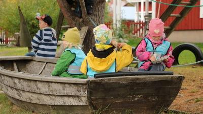 Barn sitter och leker i en eka på en dagisgård.