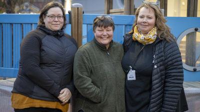 Tre kvinnor med ytterkläder står ute, utanför ett daghem (som inte syns)