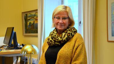 en kvinna står i sitt gula kontor med gula kläder