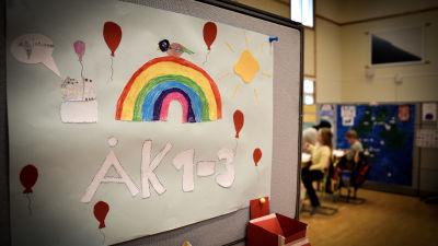 ett klassrum med barn i bakgrunden. I förgrunden en ritad affisch med en regnbåge och texten Åk 1 - 3