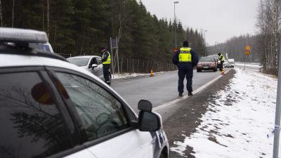 En landsväg med flera bilar som stannat och poliser i gula västar. Det finns lite snö på marken. Polisen övervakar den nyländska landsskapsgränsen.