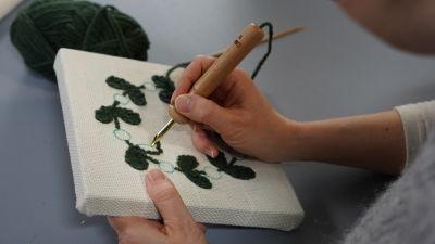 Händer som tuftar fram ett bladmotiv på ett uppspänt tyg