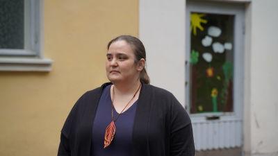en medlemålderskvinna i mörkt hår som tittar över skolgården