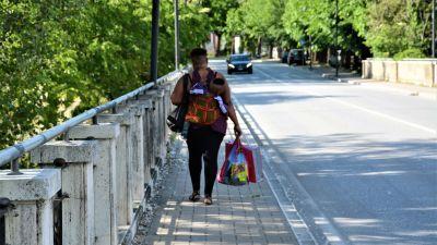 Mamma på gata med barn på ryggen.  Gatubild från staden Fabbriano.