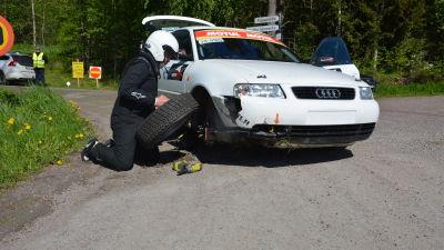 En man byter däck på en bil.