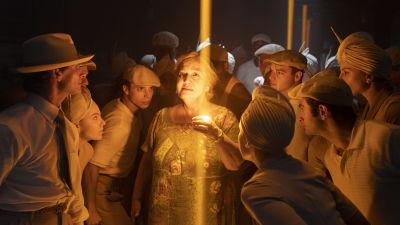 Abuela Claudia (Olga Merediz) står omringad av en massa dansare i ett mörkt utrymme med några ljusstrålar från taket.