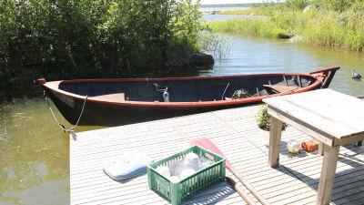 En gammal träbåt är förtöjd vid en brygga.