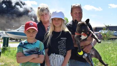 En familj på fyra personer och en hund står med det brinnande varuhuset Hurrikaani i bakgrunden.