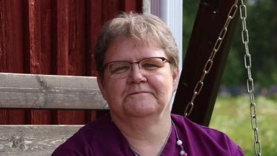 En kvinna med glasögon sitter i en gunga.
