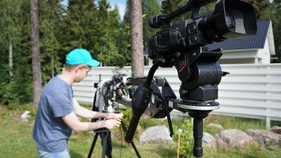 Ung man i keps och t-skjorta står vid en videokamera.