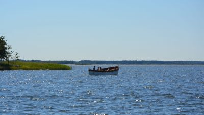 En ensam båt på vattnet en solig sommardag.