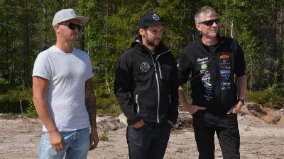 Tre män står och tittar på en motocross.