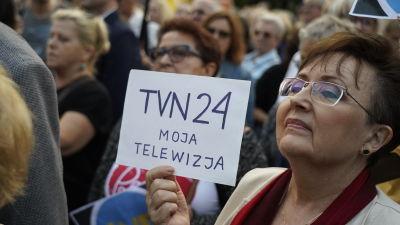 En kvinna håller upp en skylt där det står TVN24, min television.
