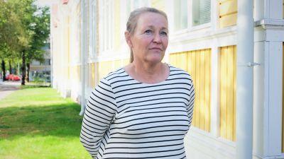 en kvinna i medelålderna med grått hår och randig skjorta som står framför ett gammalt trähus.