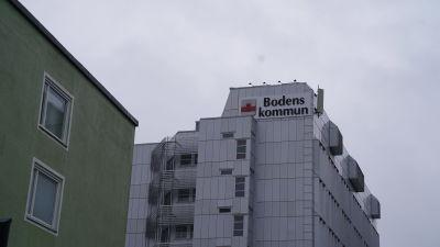 Bodens kommunhus med texten Bodens kommun. I bakgrunden regnmoln.