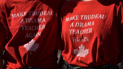 """Två demonstranter bär skjortor med texten """"Gör Justin Trudeau till dramalärare på nytt"""""""