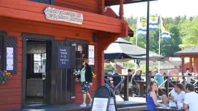 Restaurang Skeppsbron, ett rött gammaldags trähus, och folk som sitter på en terass.