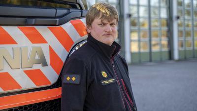 Brandmästare Henrik Hellström står vid en brandbil.