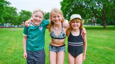Tre barn i badkläder på en gräsmatta.