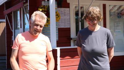 Ett medelålders par står vid en röd stuga. Mannen har en orange t-skjorta, kvinnan en blågrå.