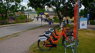 Orangefärgade cyklar står i en cykelställning.