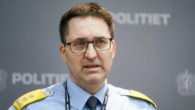 Man i polisuniform talar under en presskonferens.