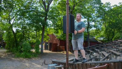 En man står uppe på kanten till en läktare och hänger upp en högtalare.