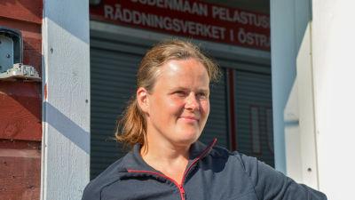 Johanna Nyholm står i solen vid dörröppningen till Wessö FBK:s brandstation.