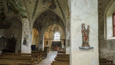 Keskiaikaisen Pyhän Ristin kirkon sisänäkymä seinä- ja kattomaalauksineen Hattulassa.