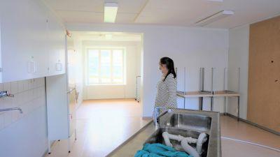 En kvinna står i ett halvfärdigt rum och tittar mot fönstret.