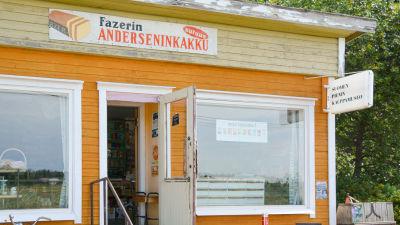 Finlands minsta butiksmuseum från utsidan. På bilden syns ett gammalt gult slitet trähus från 1958.