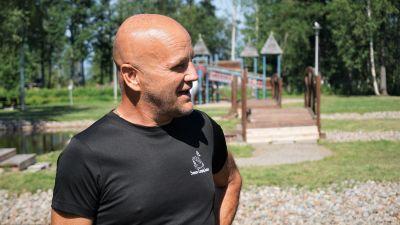 Man i svart t-skjorta står på ett campingområde.