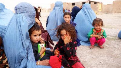 Afghanska flyktingar sitter på marken.