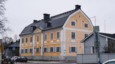 Ett gult trävåningshus med julljusstakar i fönstrena.
