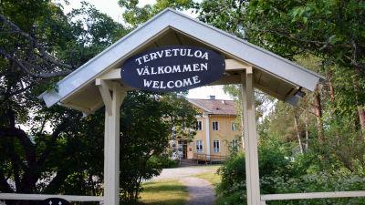 """En skylt med texten """"välkommen"""" på tre olika språk framför Sagalunds byggnad."""