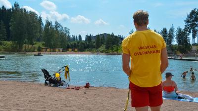 Rasmus Kettunen står och vaktar på stranden