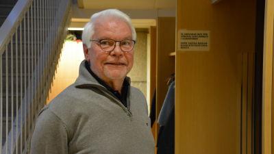 En äldre man med glasögon står och ser in i kameran.