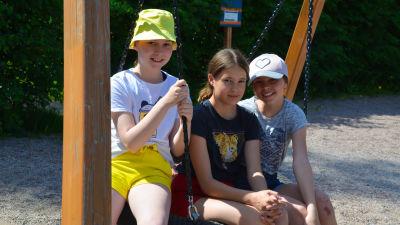 Tre flickor sitter i en gunga