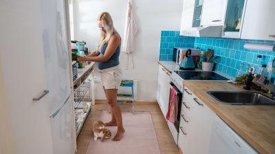 Nainen keittiössä on ojentunut ottamaan jotain tasolta. Jaloissa pupu nuuhkii naisen jalkaterää, se naurattaa naista.