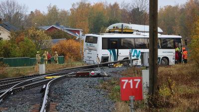 En buss ligger tvärs över en järnväg. Bakom bussen skymtar taket av en tågvagn.