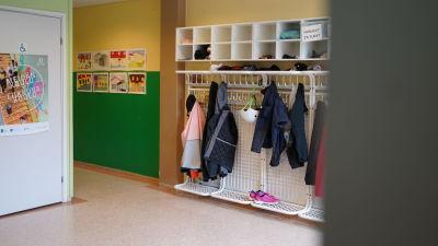 en tambur i en skola. I knaggen hänger jackor och väggarna är prydna av färgglada målningar gjorda av skolbarnen.