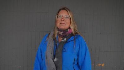Erika Andersson tittar in i kameran. I bakgrunden en grå vägg.