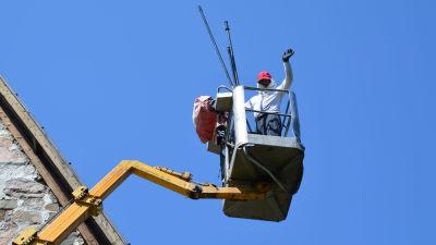 En man iklädd heltäckande kläder står i en skylift bredvid ett tak och vinkar mot kameran.