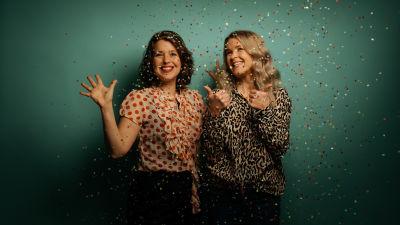 Två leende kvinnor i konfettiregn