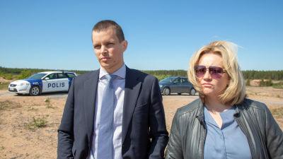 Den ledande polisduon i första säsongen av Kaikki synnit stående framför en polisbil.