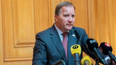 Stefan Löfven vid en pressträff i riksdagen med flera mediebolags mikrofoner framför sig.