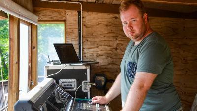 En man vid ett mixerbord och en bärbar dator.