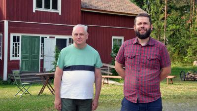 Museiguide Jarmo Kujala och museichef John Björkman framför ett rött hus på Sagalunds museum.