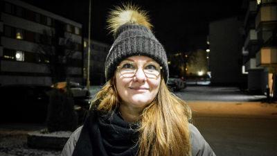 Kvinna i vintermössa och halsduk står utomhus i vintermörker och tittar in i kameran. I bakgrunden syns höghus.