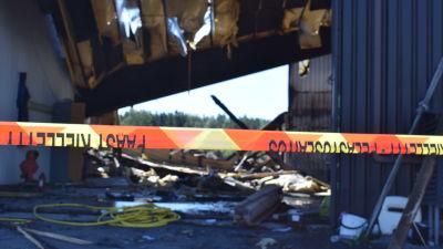 Säkerhetsband avgränsar ruiner efter brand.